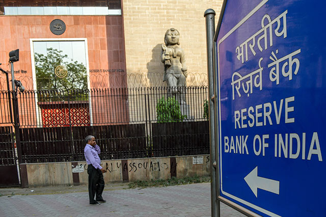 RBI keeps rates on hold, cuts growth forecast again on note ban
